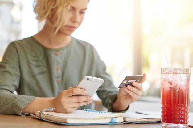 Donna bionda che tiene il telefono e la carta di credito nella caffetteria sorseggiando un drink