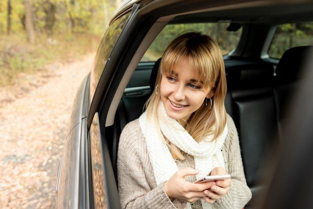 Donna bionda che tiene un telefono e distogliere lo sguardo