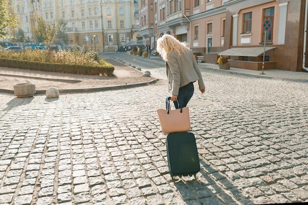 Donna bionda con borsa da viaggio