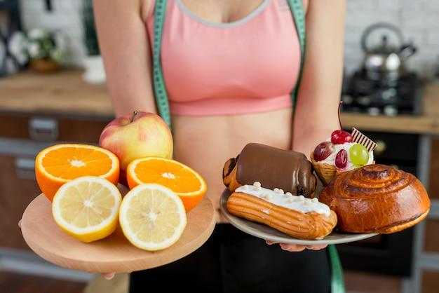 Donna bionda con frutta e pasticceria