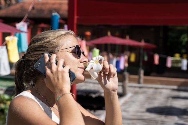 Donna bionda con gli occhiali da sole che odora un giglio bianco mentre parla sul suo cellulare davanti a una costruzione