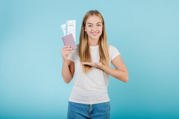 Donna bionda con i biglietti aerei e passaporto isolato sopra il blu