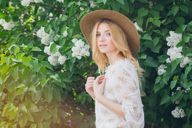 Donna bionda con i fiori lilla in primavera