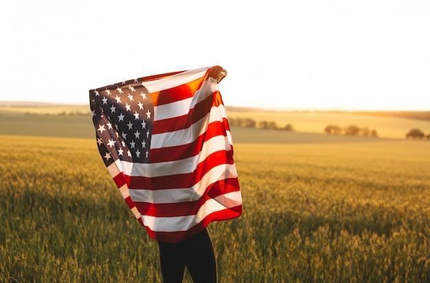 Donna bionda con la bandiera americana in esecuzione in un campo di grano al tramonto. festa dell'indipendenza, festa patriottica. 4 luglio.
