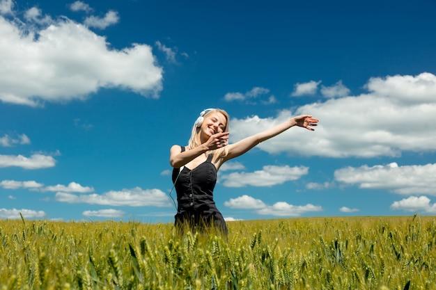 Donna bionda con le cuffie nel campo di frumento nel giorno soleggiato