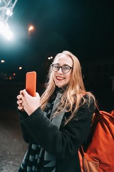 Donna bionda con lo smartphone di notte in strada.