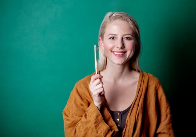 Donna bionda con spazzolino da denti in legno sulla scena verde