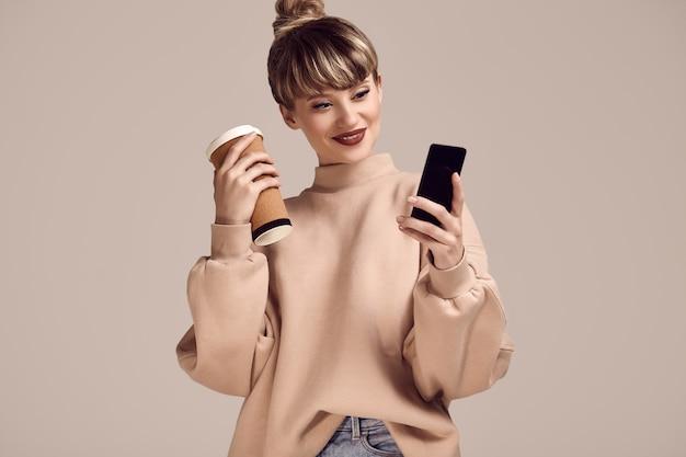 Donna bionda dei pantaloni a vita bassa di bello fascino con la tazza di caffè e il telefono
