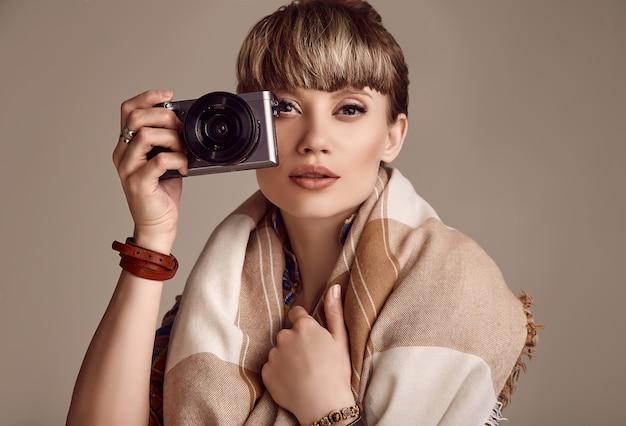Donna bionda del hippie di bello fascino che prende immagine sulla macchina fotografica