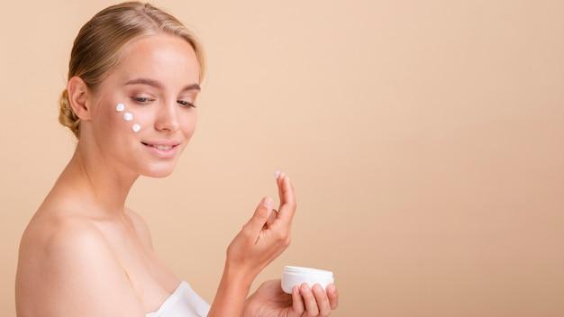 Donna bionda del primo piano con crema sul suo fronte