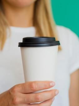 Donna bionda del primo piano con la tazza di caffè e la priorità bassa verde