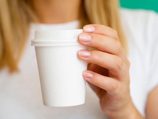 Donna bionda del primo piano con la tazza di caffè