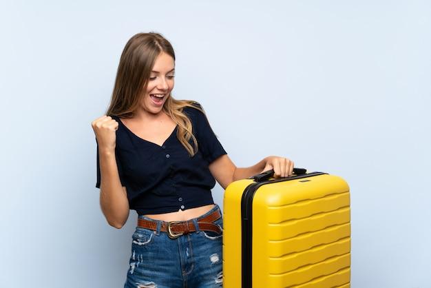 Donna bionda del viaggiatore con la valigia che celebra una vittoria