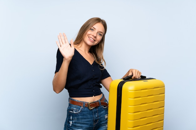 Donna bionda del viaggiatore con la valigia che saluta con la mano con l'espressione felice