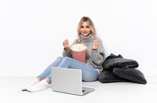 Donna bionda dell'adolescente che mangia popcorn mentre guardando un film sul computer portatile che fa gesto dei soldi
