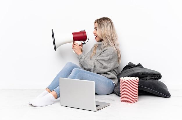 Donna bionda dell'adolescente che mangia popcorn mentre guardando un film sul computer portatile che grida tramite un megafono