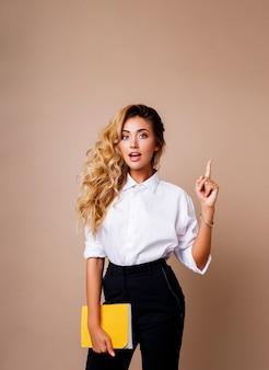 Donna bionda di affari che indica in su e che osserva sulla parete beige. indossa abiti da lavoro eleganti. copia spazio per il testo. volto a sorpresa.