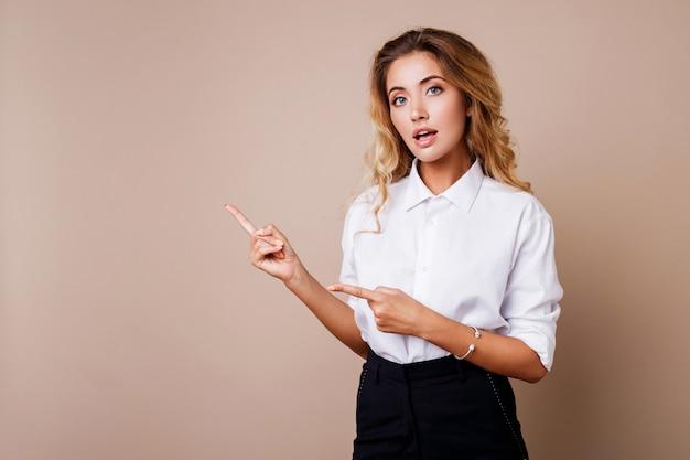 Donna bionda di affari che indica in su e che osserva sulla parete beige. indossa abiti da lavoro eleganti. copia spazio per il testo.