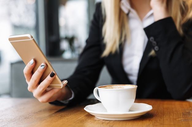 Donna bionda di affari che si siede all'interno in caffè