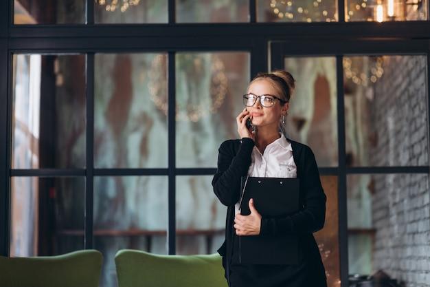 Donna bionda di affari che si siede sull'area di lavoro e che utilizza computer portatile all'ufficio, esamina una cartella con i documenti, parlando dal telefono e sta bevendo la tazza di caffè.