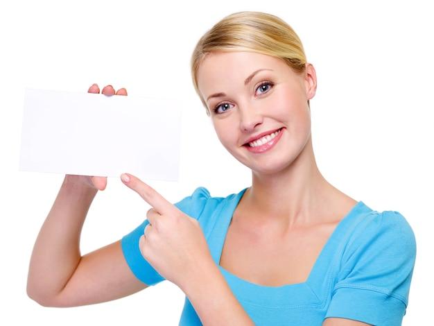 Donna bionda di bellezza che indica sulla scheda bianca in bianco - isolata su bianco
