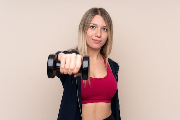 Donna bionda di giovane sport che fa sollevamento pesi