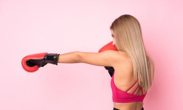 Donna bionda di giovane sport con i guantoni da pugile sopra il rosa isolato