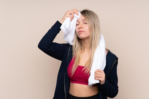 Donna bionda di giovane sport con l'asciugamano di sport