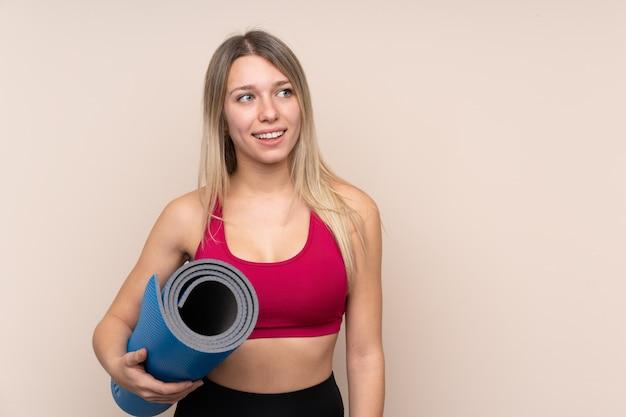 Donna bionda di giovane sport con una stuoia e sorridere