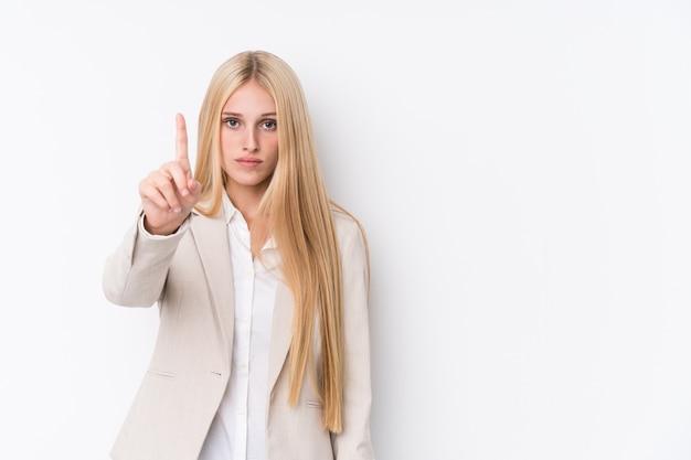 Donna bionda di giovani affari su fondo bianco che mostra numero uno con il dito.