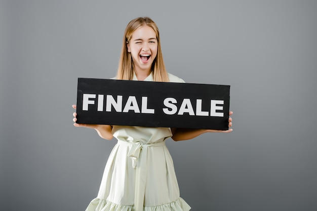 Donna bionda di grido felice con il segno di vendita finale isolato sopra grey