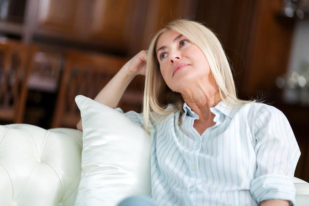Donna bionda di mezza età adorabile con un sorriso raggiante che si siede su un sofà a casa
