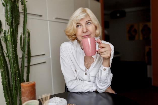 Donna bionda di mezza età attraente che si rilassa a casa sulla cucina e che beve caffè