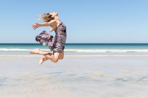Donna bionda di mezza età in un vestito verde che salta sulla spiaggia