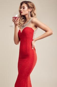 Donna bionda elegante splendida che porta vestito rosso da modo