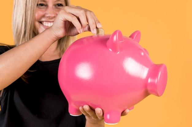 Donna bionda felice che inserisce moneta dentro il porcellino salvadanaio rosa