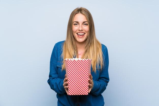 Donna bionda felice con popcorn sopra la parete blu