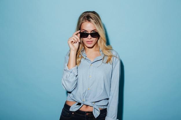 Donna bionda fresca in camicia e occhiali da sole che guarda l'obbiettivo