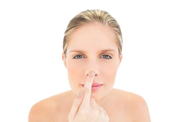 Donna bionda fresca pacifica che tocca il suo naso