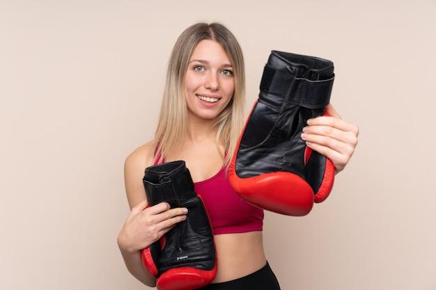 Donna bionda giovane sportivo con guantoni da boxe