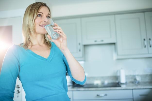 Donna bionda graziosa che beve un bicchiere d'acqua