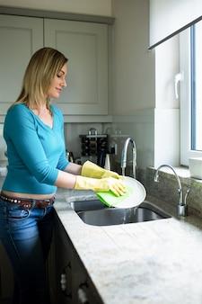 Donna bionda graziosa che fa i lavoretti della casa