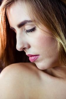 Donna bionda graziosa che la chiude occhi