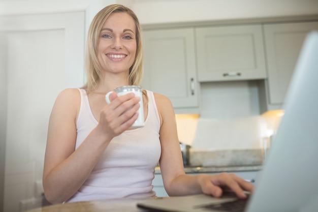 Donna bionda graziosa che mangia caffè e che per mezzo del computer portatile