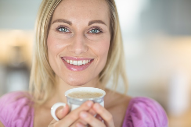 Donna bionda graziosa che mangia caffè