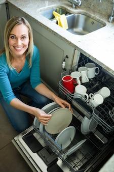 Donna bionda graziosa che svuota la lavastoviglie