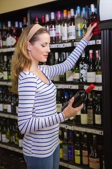 Donna bionda graziosa che tiene una bottiglia di vino rosso