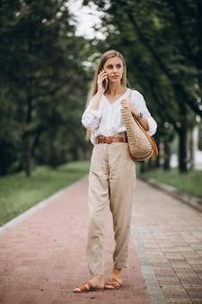 Donna bionda graziosa che utilizza telefono fuori nel parco