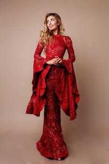 Donna bionda graziosa nella posa elegante del vestito dal nuovo anno. maniche larghe insolite. capelli mossi. a tutta altezza.