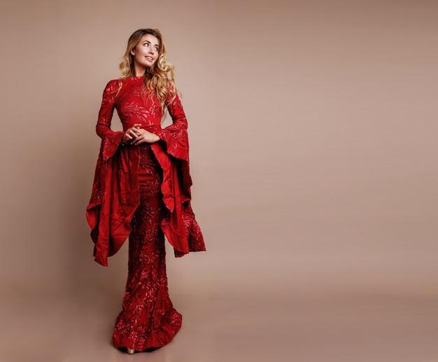Donna bionda graziosa nella posa elegante del vestito dal nuovo anno. maniche larghe insolite. capelli mossi.